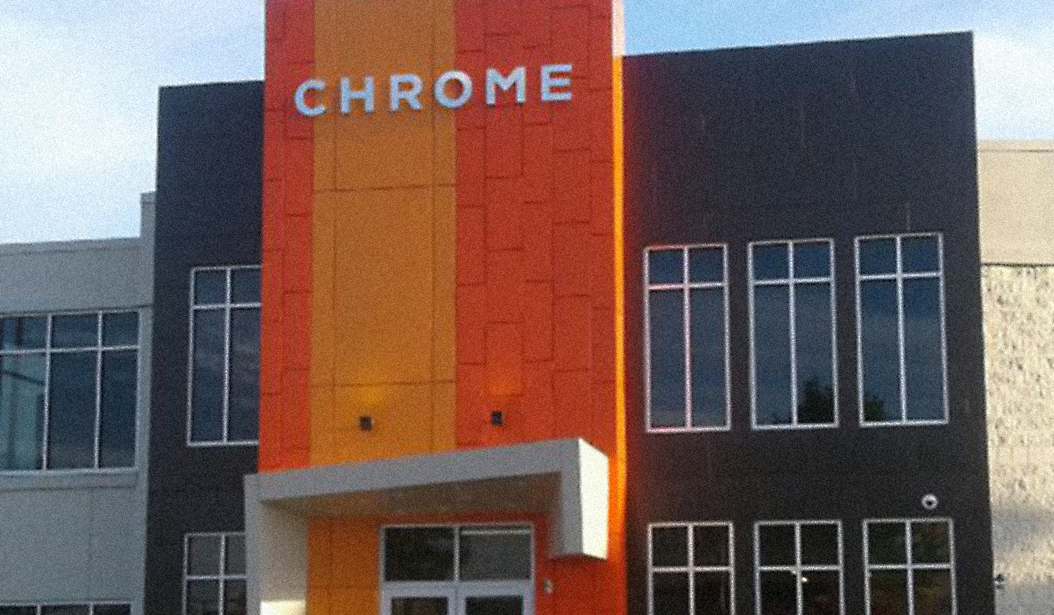 Various shapes and sizes of bright colored orange and yellow aluminum composite material paneling on the front of a modern looking financial institution