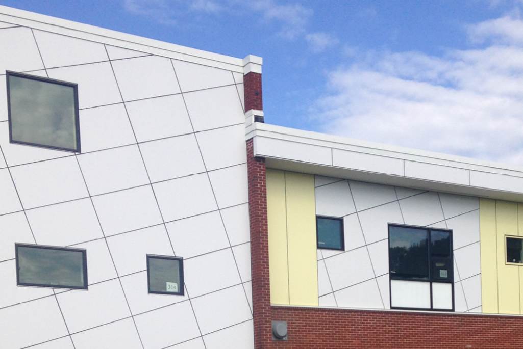 White and yellow ACM paneling, in various geometric shapes and patterns, displayed throughout the exterior of a school building in Pennsylvania