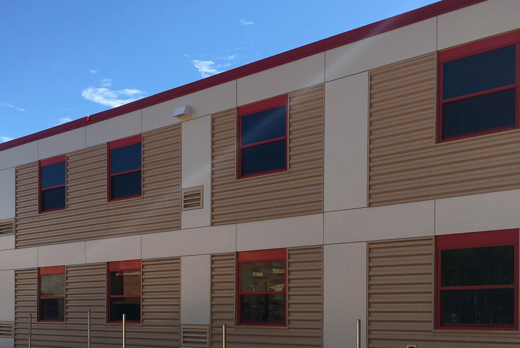 Beige, brown and red aluminum composite paneling with red metal window accents installed on the exterior of an elementary school building