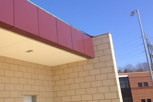 Red and beige rain screen, aluminum composite material system installed onto an entry way on the outside of a medical center in northeast Ohio