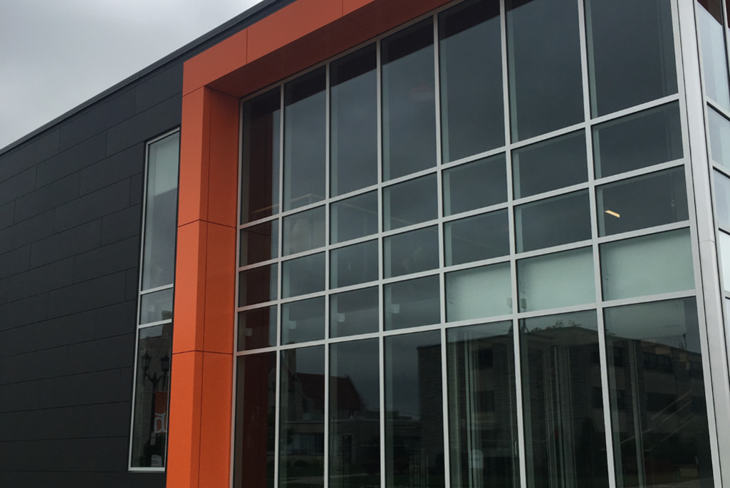 Close-up image of modern metallic orange and black paneled rain screens installed on the exterior of a university in Tiffin, Ohio